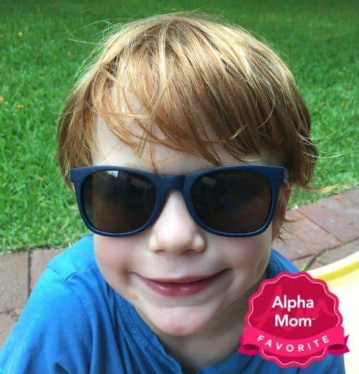 A boy wearing dark blue Knockaround Sunglasses