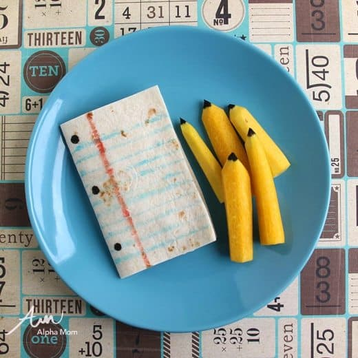 paper and pencil after school snack on a blue plate (made with tortillas and yellow carrots)