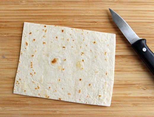 a tortilla cut into a square shape laying next to a kitchen knife