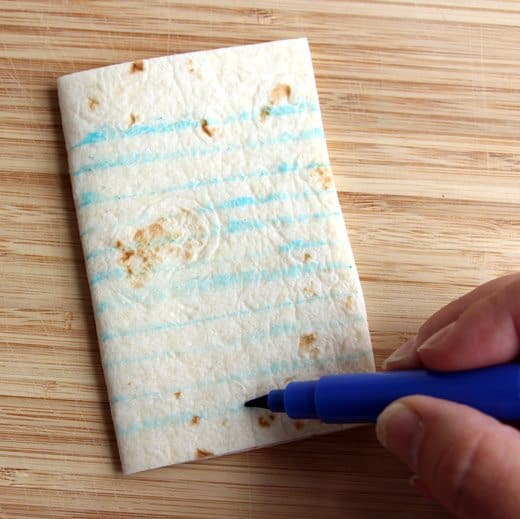 making lines on a square piece of tortilla using a blue food safe marker