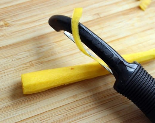 peeling a yellow carrot with a black food peeler