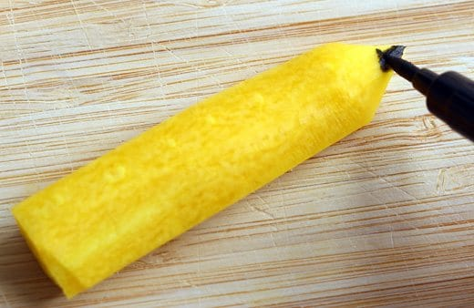 a black food safe marker being used to color the tip of a yellow carrot that has been cut in the shape of a pencil