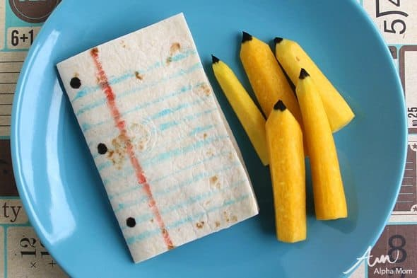 paper and pencil snack made with yellow carrots and tortillas on a blue plate