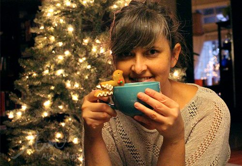 woman holding a coffee cup with a gingerbread bird cookie perched on the side in front of a christmas tree