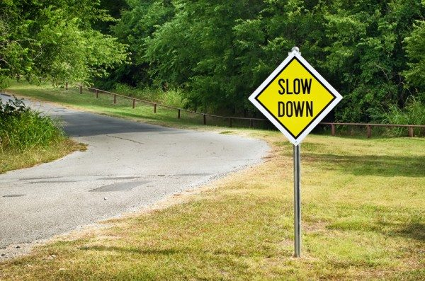 Slow Down sign on the side of a single land road