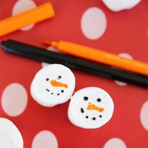 Snowman faces drawn on large marshmallows
