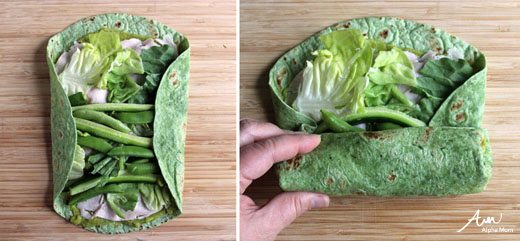 rolling up sandwich wrap with veggies