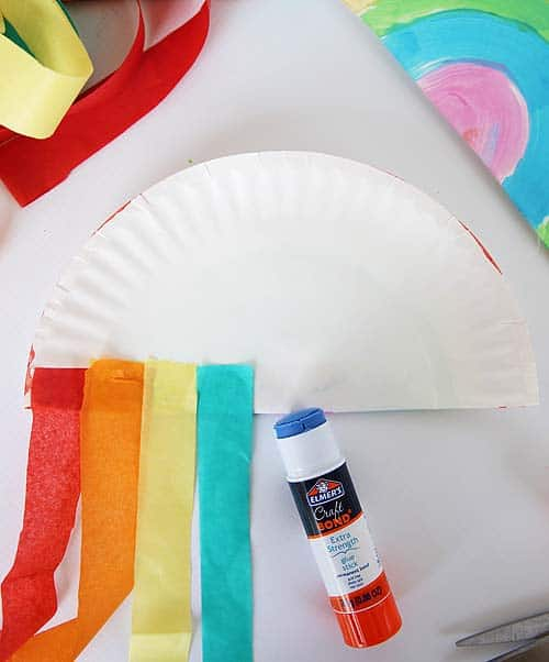 tissue paper strips being glued onto paper plate