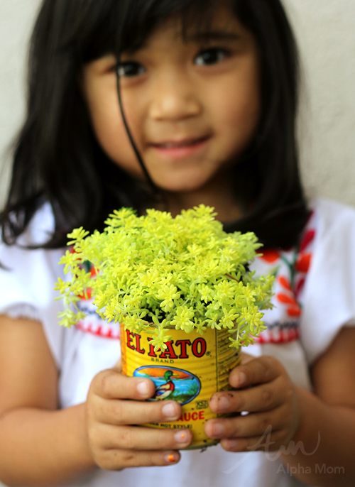 A child holding plant potted in old food can