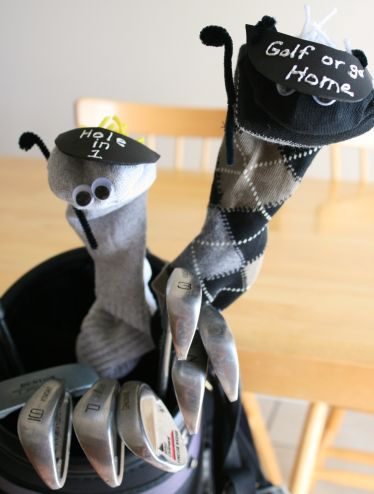 Homemade golf cover sock puppets on a pair of golf clubs