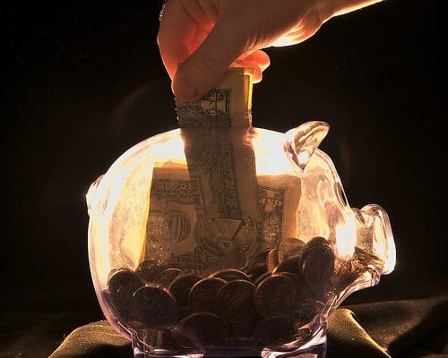 A dollar being placed inside a clear piggy bank
