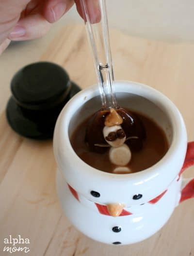 chocolate dipped spoon dipped into hot chocolate in a snowman mug