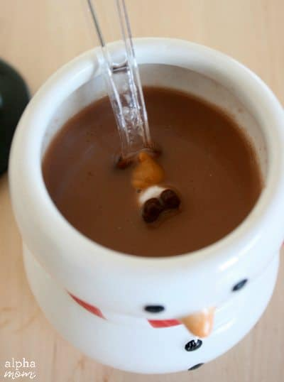 chocolate covered spoon melting in mug of hot cocoa