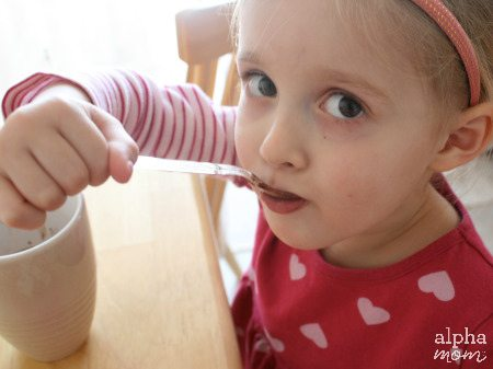 Child licking a chocolate covered spoon