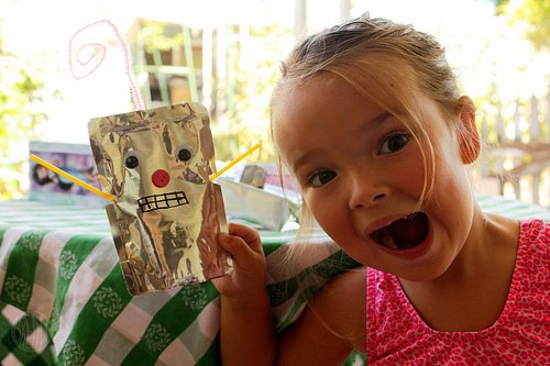 "Smiling child holding up a ""robot"" she made out of recyclable lunch box items"