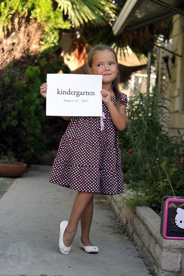 young girl in a dress holding a piece of paper that says kindergarten
