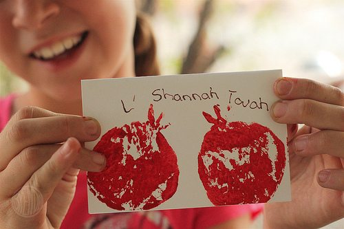 closeup picture of girl holding handmade Rosh Hashanah card with painted pomegranate and L'Shana Tovah message