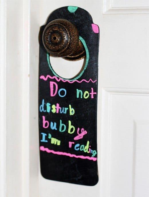 Black chalkboard paint door hanger hanging from a door knob