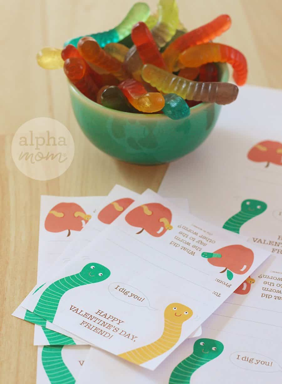 Bowl of gummy worms sitting next to valentines day printable