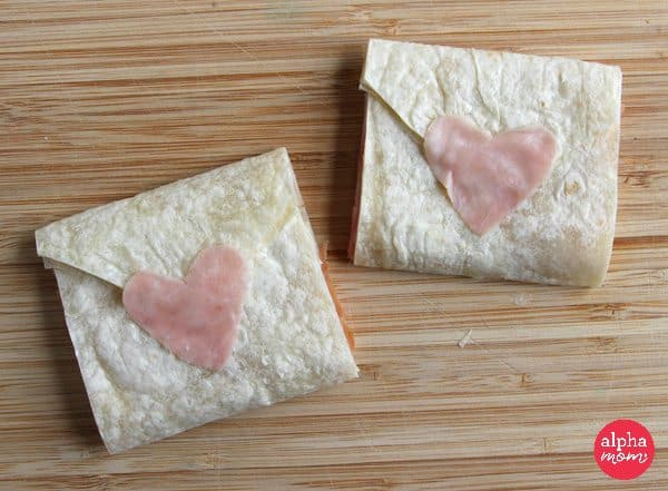 Tortillas shaped as envelopes sealed with heart shaped pieces of ham