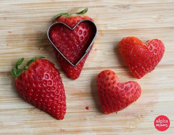 cutting out heart shaped strawberries
