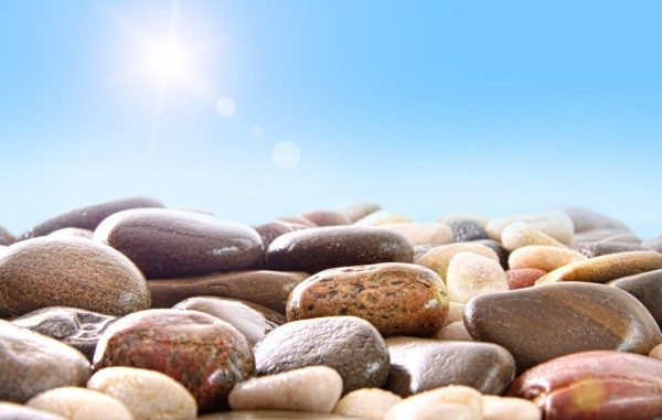 Pile of rocks laying on the ground under a sunny blue sky