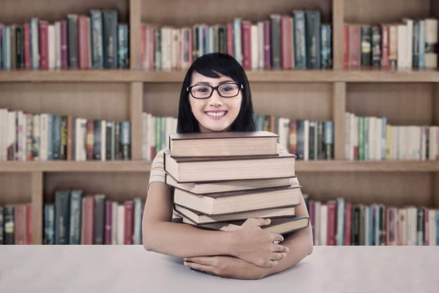 College student sitting in a library with a stack of books