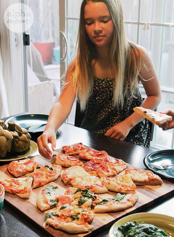 tween girl reaching for slice of homemade pizza