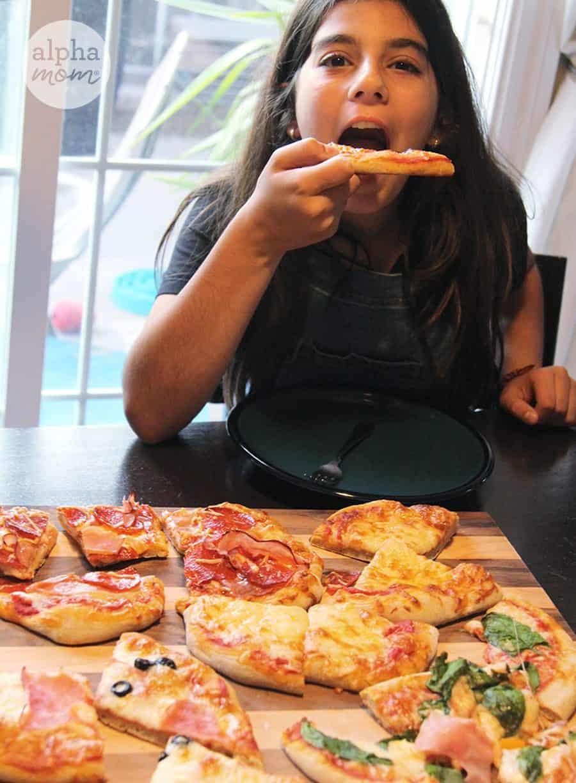 brunette tween girl eating a slice of homemade pizza