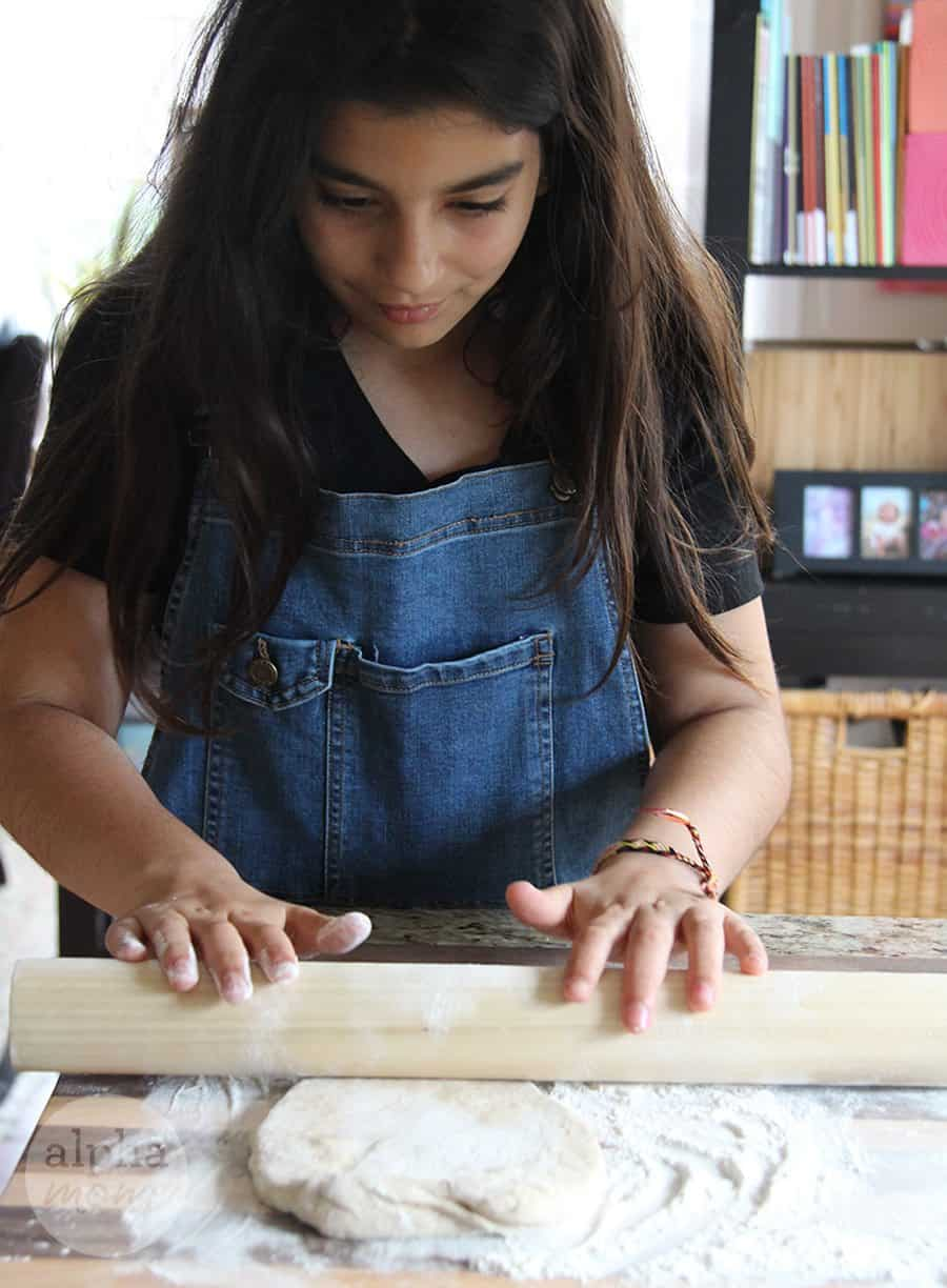 tween girl rolling out pizza dough
