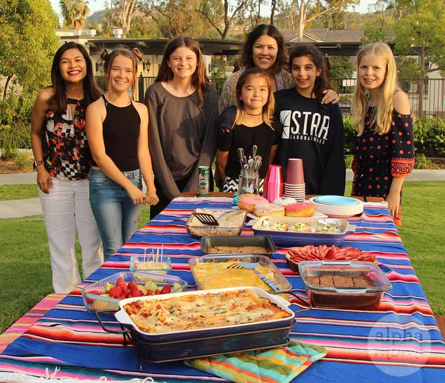 A group of friends posing in front of a table of potluck food