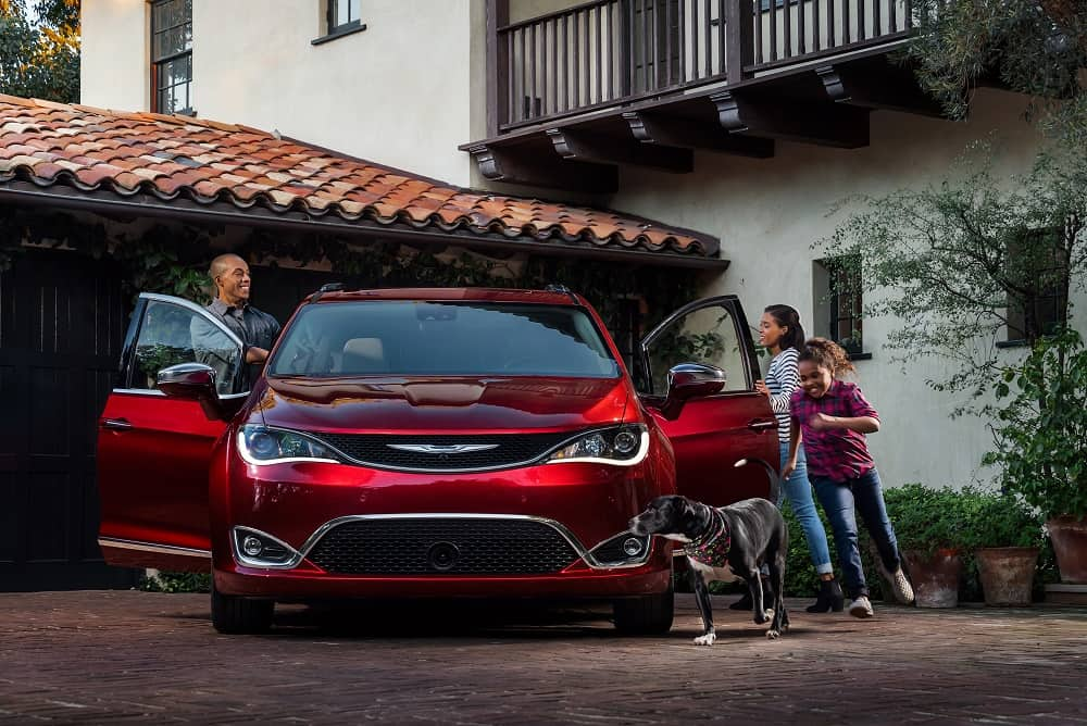 Family getting into a red Chrysler Minivan