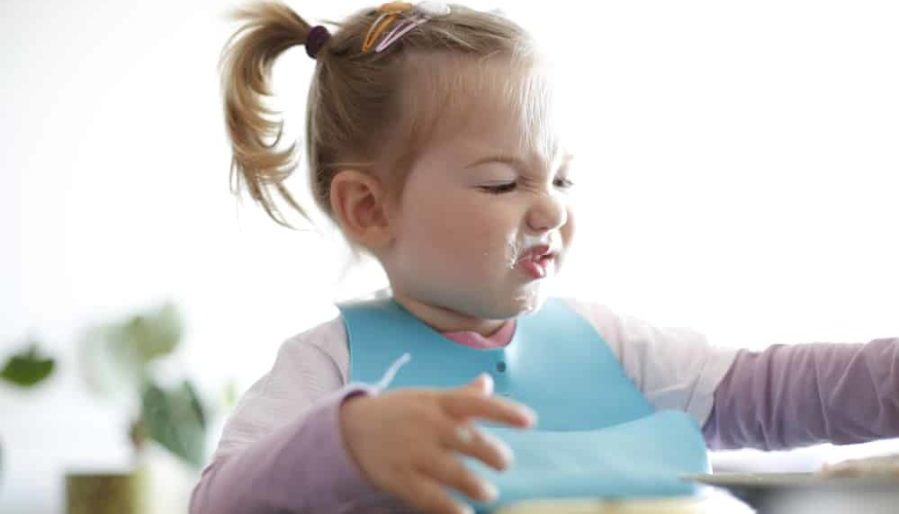 Little girl toddler picking her food and making faces