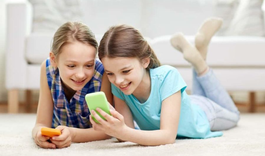 happy little girls with smartphones lying on floor at home