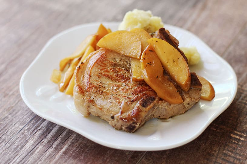Side view of pork chops and apples on a plate with mashed potatoes
