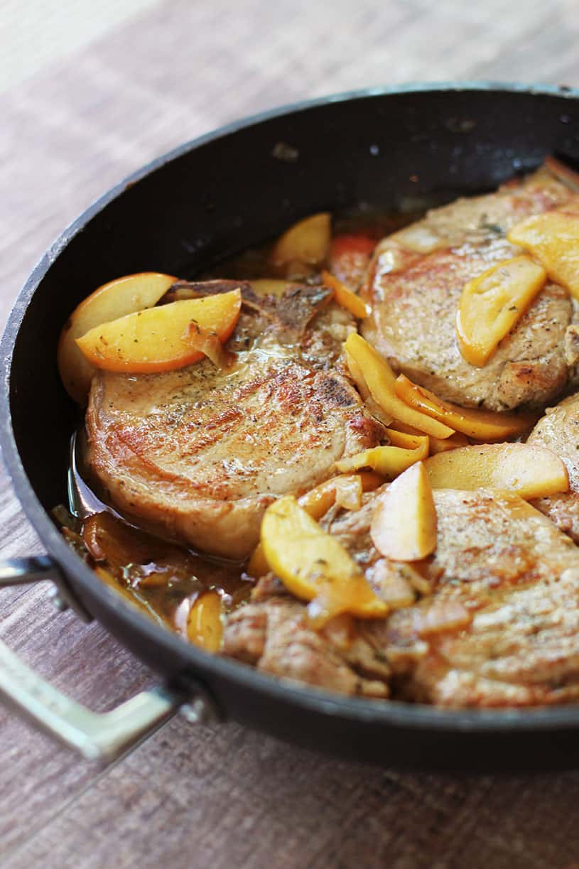Side view of pork chops and apples recipe in the pan