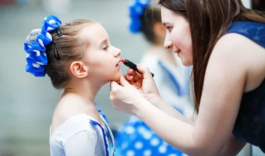 Mother putting lipstick on her daughter before a dance performance
