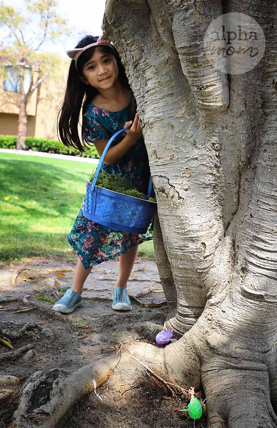 school girl on easter egg hunt near tree