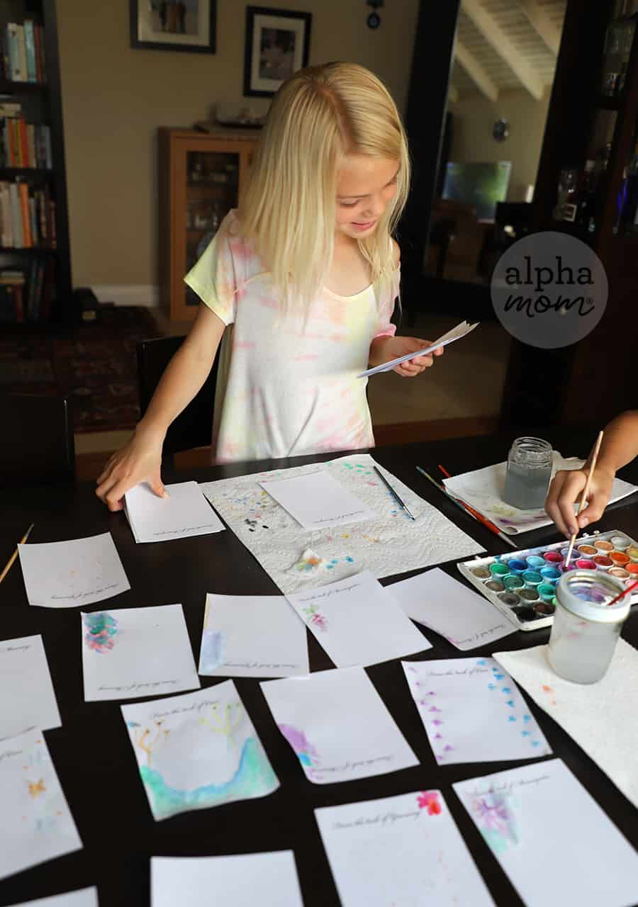 smiling girl looking at her watercolor craft with papers drying on table