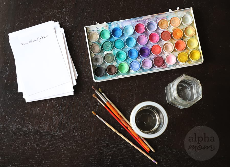 watercolor paints, paintbrushes and handmade notepad