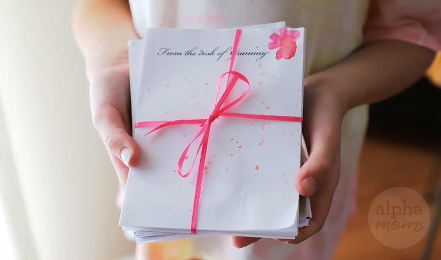 "Close-up of child holding a gift of handmade notepad reading ""From the desk of Grammy"""