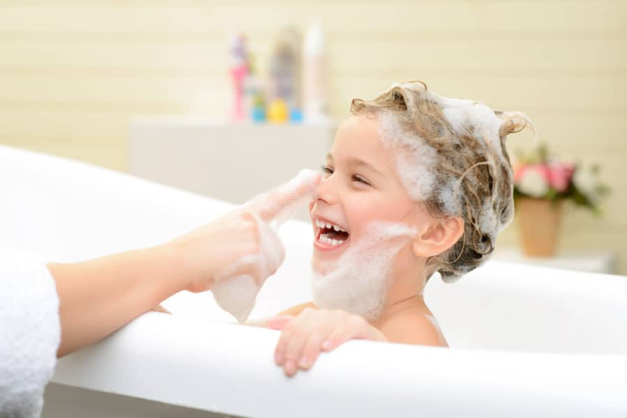 Cute smiling little girl sitting in the bath tube and taking bath while having fun with her mother
