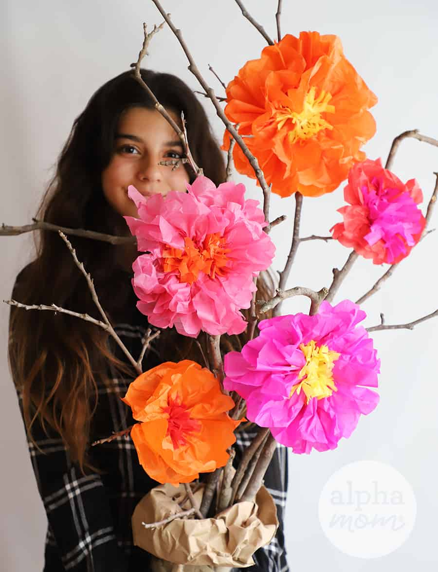 teen girl holding bouquet of tall branches with large orange and hot pink crepe tissue flowers