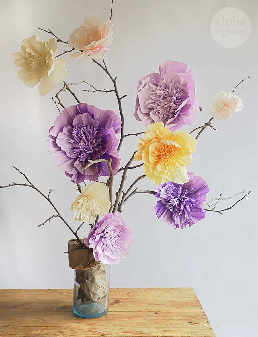 tall branches decorated with large purple, yellow, light pink and cream crepe tissue flowers in a vase