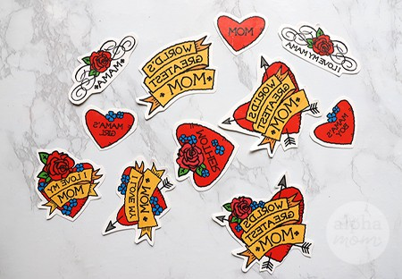 close-up of cut out temporary tattoos of hearts and arrows for Mother's Day saying World's Greatest Mom and Mom and more
