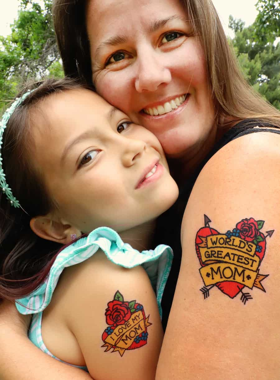 close-up of mother and daughter hugging and showing off their temporary tattoos on their arms that read World's Greatest Mom and I Love My Mom