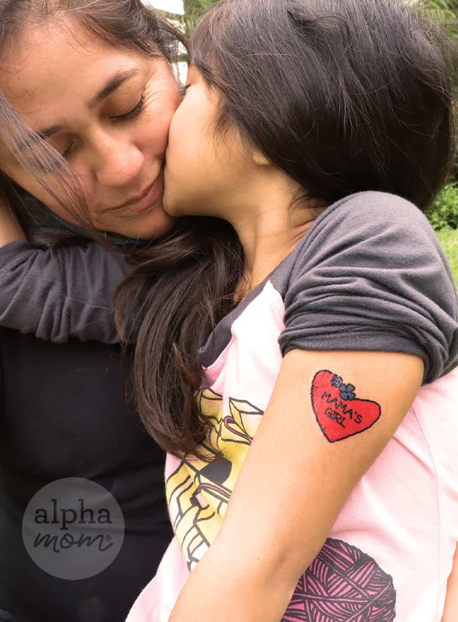 daughter giving mom a kiss and showing off her temporary tattoos on her arms that reads Mama's Girl