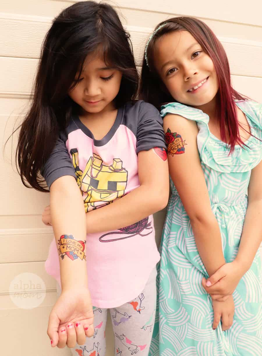 two girls showing off their temporary tattoos on their arms that read I Love My Mom