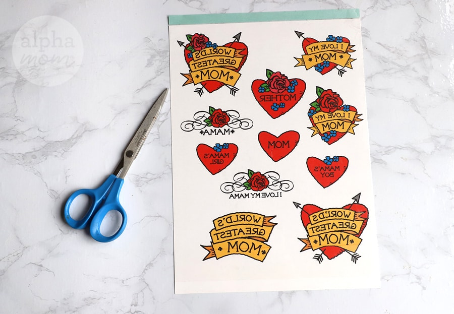 temporary tattoos shaped like hearts for Mother's Day on a sheet of paper and scissor nearby