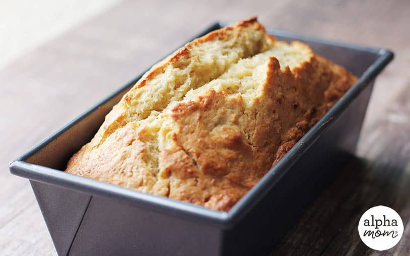 Side view of banana bread in a pan, backlit